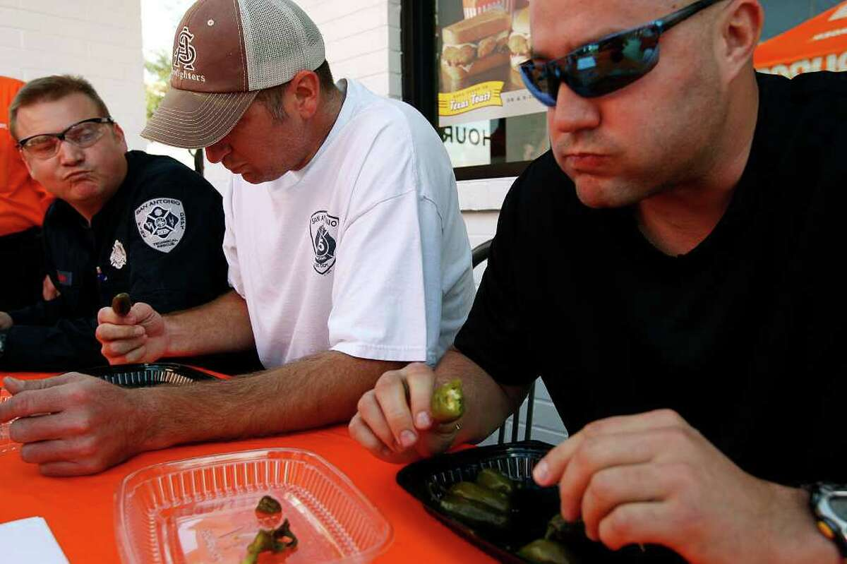 METRO -- Members of the San Antonio Fire Department work compete against the San Antonio Police Department in the second annual Jalapeno Eating Contest sponsored by Whataburger, Tuesday, Feb. 15, 2011. SAFD took the honors by eating 23 peppers while the police department came in at 19 peppers. They are from left, Engineer Jeff Mahan, Engineer Bob Beckett and Firefighter Clint Spencer. First place won $750 while the second place was $250 with the prize money going to the 100 Club of San Antonio. The non-profit helps support families of firefighters and peace officers who die in the line of duty. JERRY LARA/glara@express-news.net