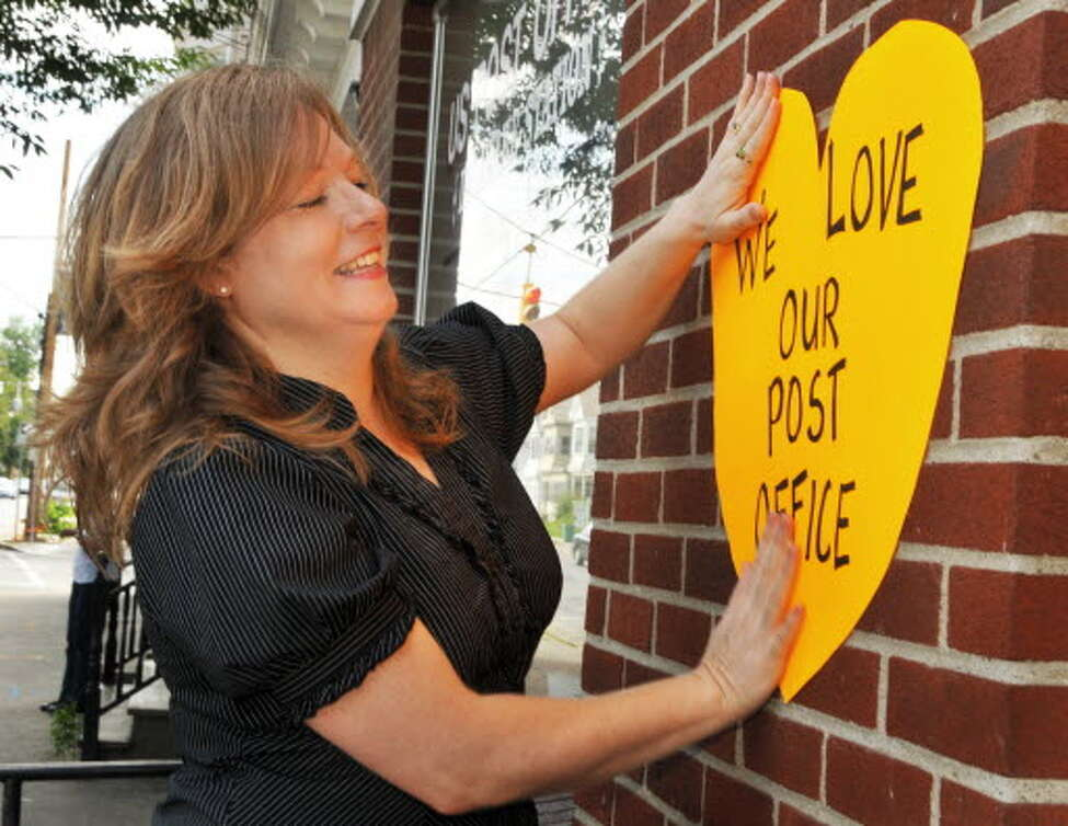 Laura Welles, a Delaware Avenue resident, hangs a sign for a rally to save the Delaware Station Post Office on Tuesday, August 11, 2009. (John Carl D'Annibale / Times Union archive)