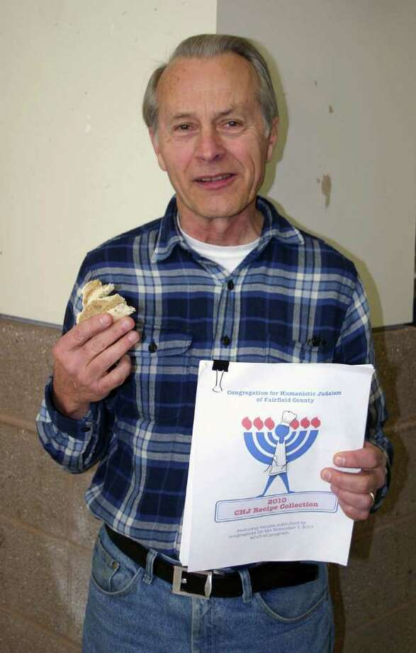Fairfield resident and co-director of adult education at the Congregation for Humanistic Judaism, enjoys a bagel and lox and displays the recipe collection he is compiling for a program on Jewish foods. Photo: Contributed Photo / Westport News