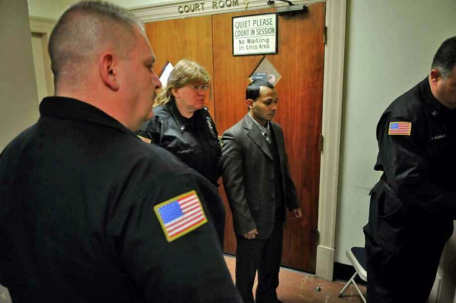 Defendant  Adrian Parbhudial, center, is led by Schenectady County Sheriff's Department members into a holding room outside of a courtroom in the Schenectady County Courthouse during a break in his trial in Schenectady, NY on Wednesday February 16, 2011.  ( Philip Kamrass / Times Union ) Photo: PHILIP KAMRASS