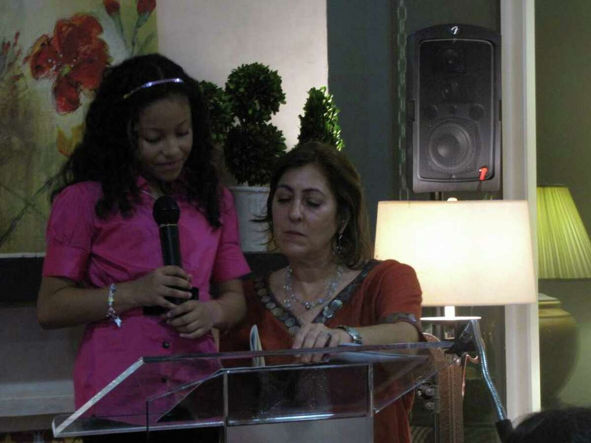"""Shanique Martinez, accompanied by clinical director Patricia McNaught, reads a poem during Friday's """"An Evening of Poetry as Joy and Healing"""" at the Children's Bereavement Center of South Texas."""
