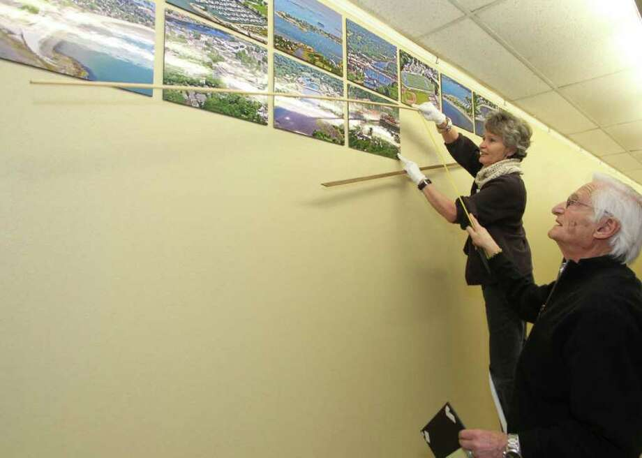 Westport photographer Larry Untermeyer helps Ellen Naftalin of the Westport Historical Society hang 48 of his aerial photographs of the town in a new exhibit at Westport Town Hall. Photo: Contributed Photo / Westport News contributed