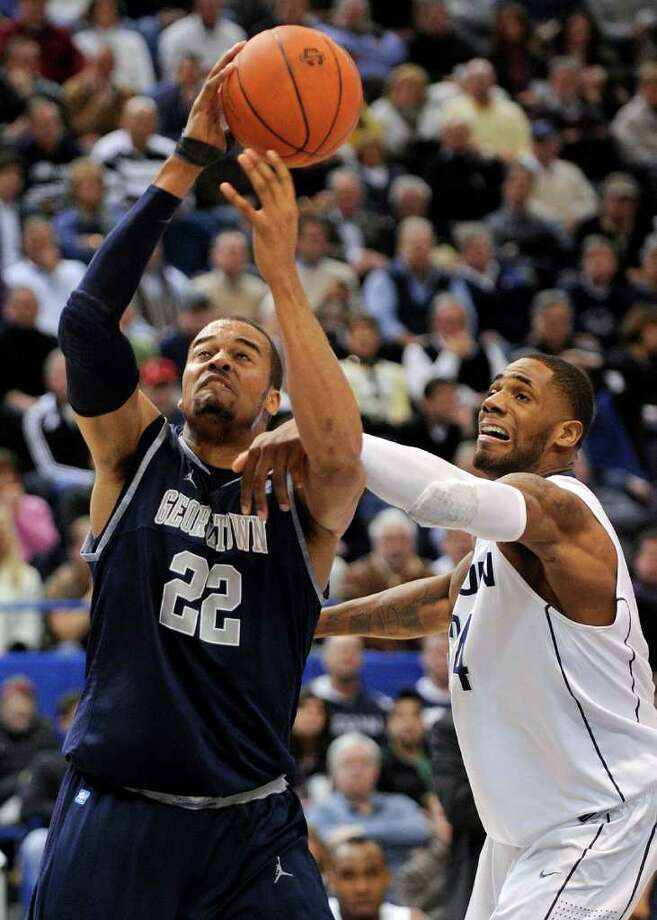 Connecticut's Alex Oriakhi, right, fouls Georgetown's Julian Vaughn during the first half of an NCAA college basketball game in Hartford, Conn., on Wednesday, Feb. 16, 2011.  (AP Photo/Fred Beckham) Photo: AP
