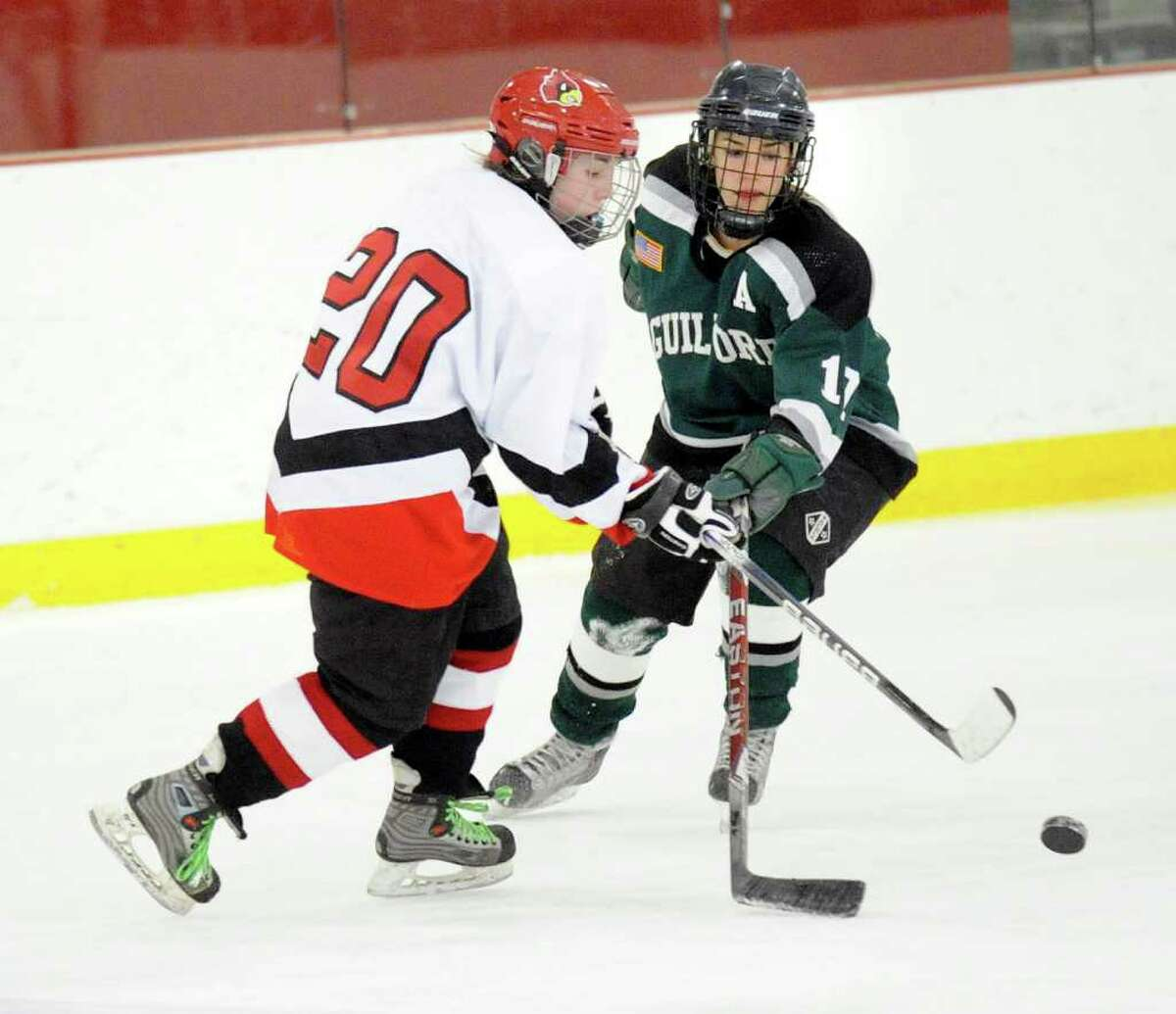 Erin Ferguson, # 20 of Greenwich High School, left, shoots while being covered by Ali Putney, # 17 of Guilford High School, right, during girls ice hockey game between Greenwich High School and Guilford High School at Hamill Rink, Byram, Tuesday, Feb. 15, 2011.