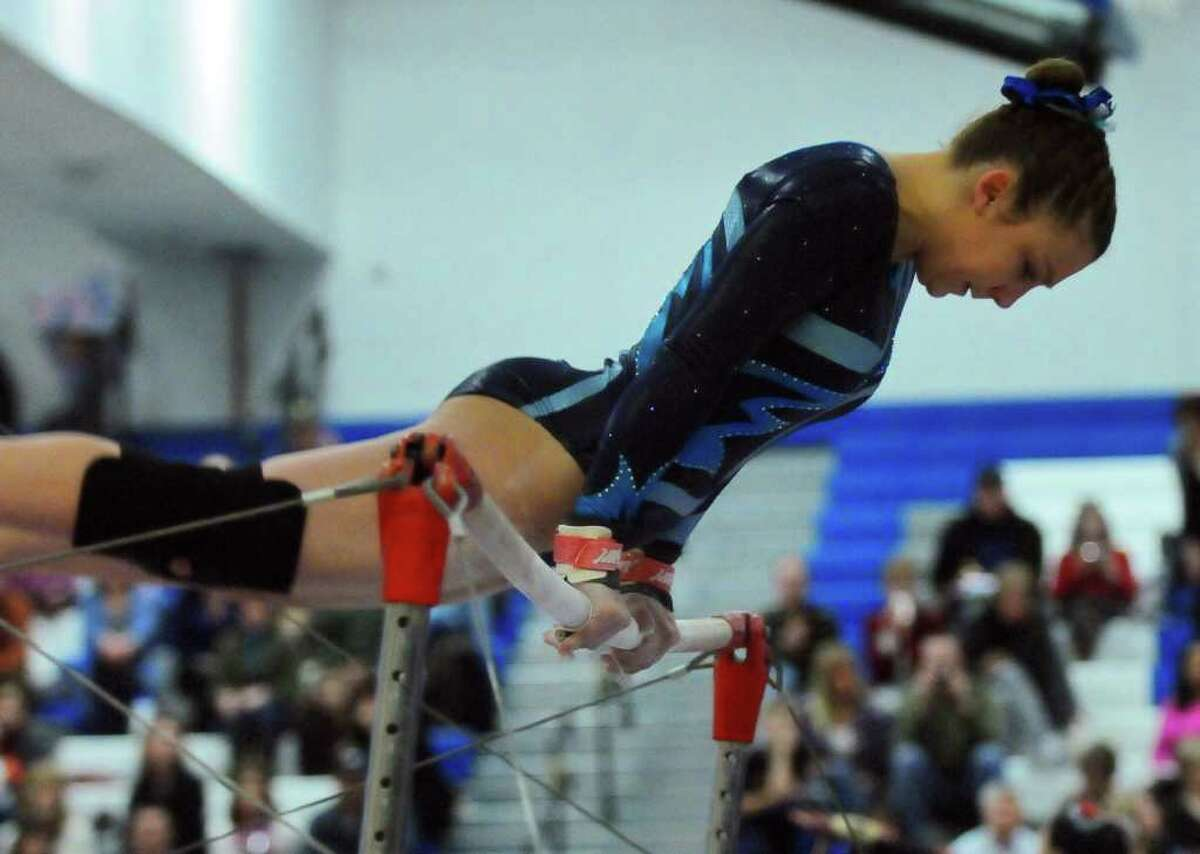 Saratoga's Tiffany Hogben performs on the uneven bars at the Section II gymnastics championship at Shaker High School in Latham, NY, on Wednesday 2/16/11. ( Philip Kamrass / Times Union )