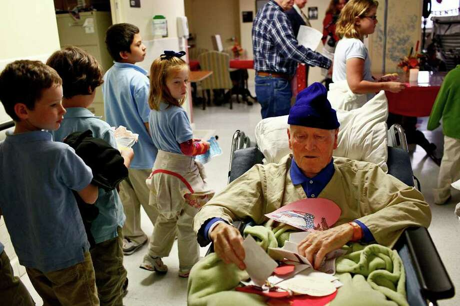 Air Force Veteran Perry Baycroft looks through valentines given to him by students from the Hill Country Adventist School during their visit Wednesday. Photo: LISA KRANTZ, SAN ANTONIO EXPRESS-NEWS / SAN ANTONIO EXPRESS-NEWS