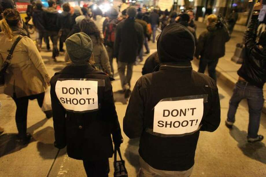Protesters march down Fourth Avenue on Wednesday night bearing a message for local police. Photo: Joshua Trujillo/seattlepi.com