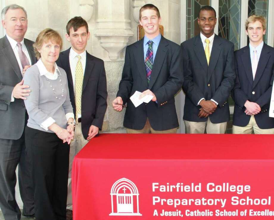 Mike and Kathleen Sweeney, at left, who won Fairfield Prep's tuition raffle last year, are shown with their son, senior Mike Sweeney, buying a ticket in this year's $25,000 raffle from senior student government members C.J. Donahue, Jesus Fequiere and Matt Fornshell. Photo: Contributed Photo / Fairfield Citizen contributed