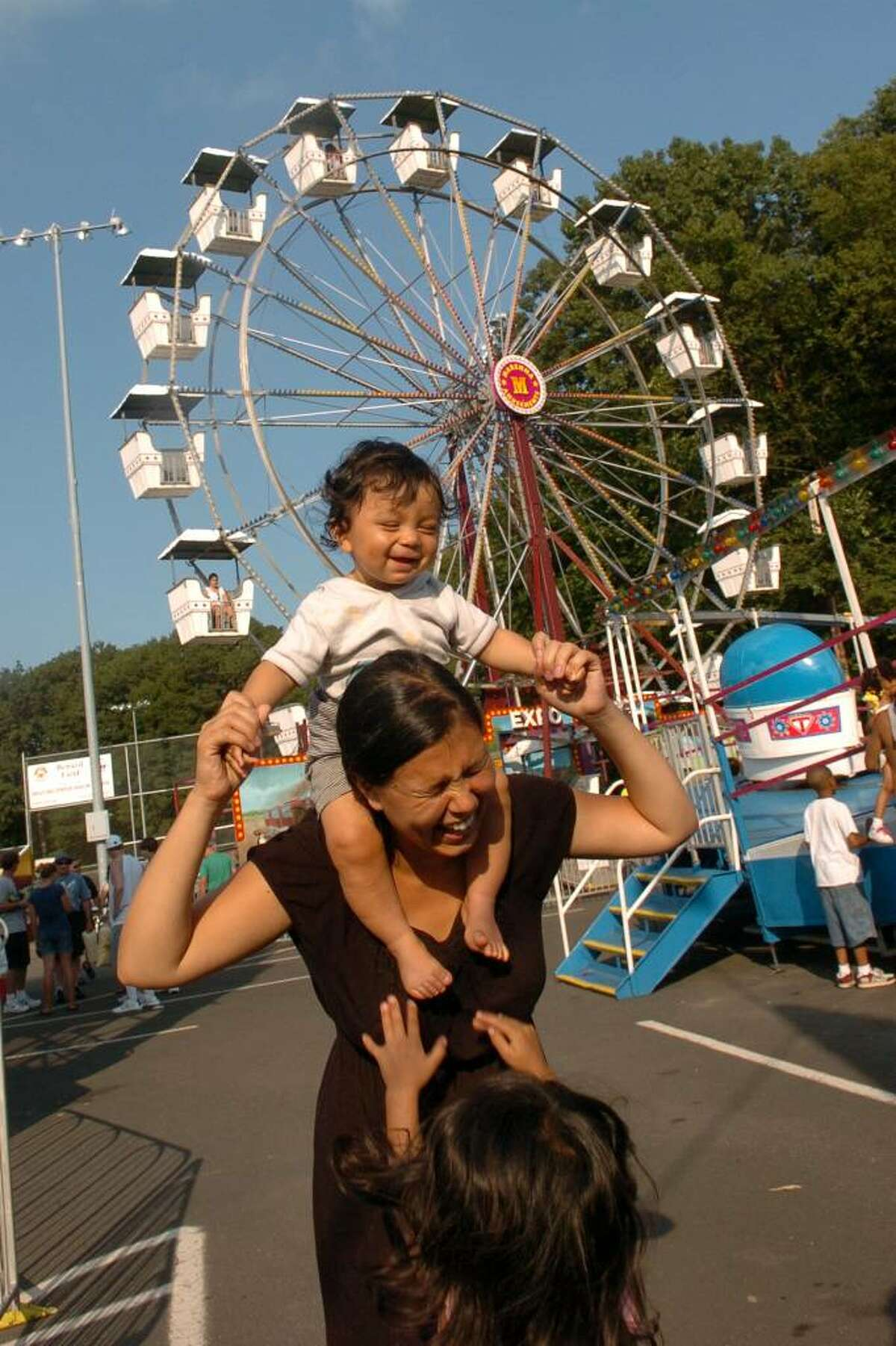 Christian Abraham/Staff photographer Members of the Shah family enjoy the amusements, during the Milford Oyster Festival in downtown Milford, CT on Saturday August 15, 2009. Here, Nadine Shah, of Milford, holds her son Miro, 9 months, on her shoulders as her daughter Amila, 4, jumps up for a turn to be held. Not pictured is Nadine's husband, Atit, who was snapping pictures of them also.