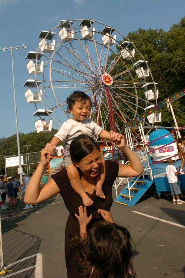 Christian Abraham/Staff photographer Members of the Shah family enjoy the amusements, during the Milford Oyster Festival in downtown Milford, CT on Saturday August 15, 2009. Here, Nadine Shah, of Milford, holds her son Miro, 9 months, on her shoulders as her daughter Amila, 4, jumps up for a turn to be held. Not pictured is Nadine's husband, Atit, who was snapping pictures of them also. Photo: Christian Abraham / Connecticut Post