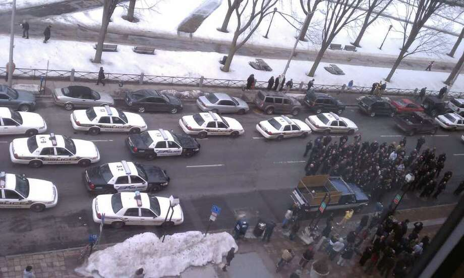 """With their lights flashing and their sirens blaring, New Haven police officers drove up to City Hall on Thursday, Feb. 17, got out of their vehicles and started chanting """"Bring Them Back!"""" in response to 16 layoffs recently announced by the city. Photo: WTNH/T.J. Tatroe"""