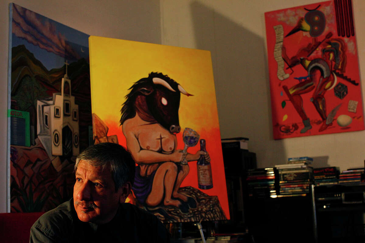 """Artist Norman René Avila at his apartment with his work, including """"Sangre de Toro"""" (center) and """"Vindication 1"""" (right). His art will be part of the On and Off Fredericksburg Road Studio Tour this weekend. LISA KRANTZ / EXPRESS-NEWS"""