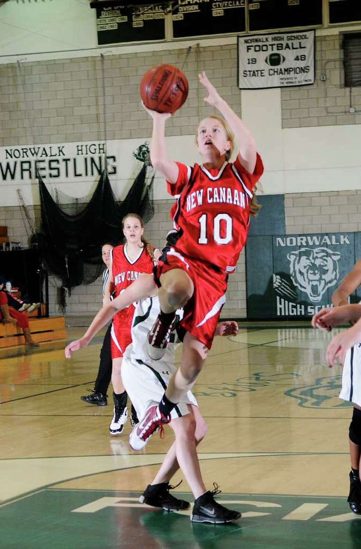 New Canaan's Sarah Mannelly drives to the hoop as Norwalk High School hosts New Canaan High School in Norwalk, CT on Monday January 10, 2011.