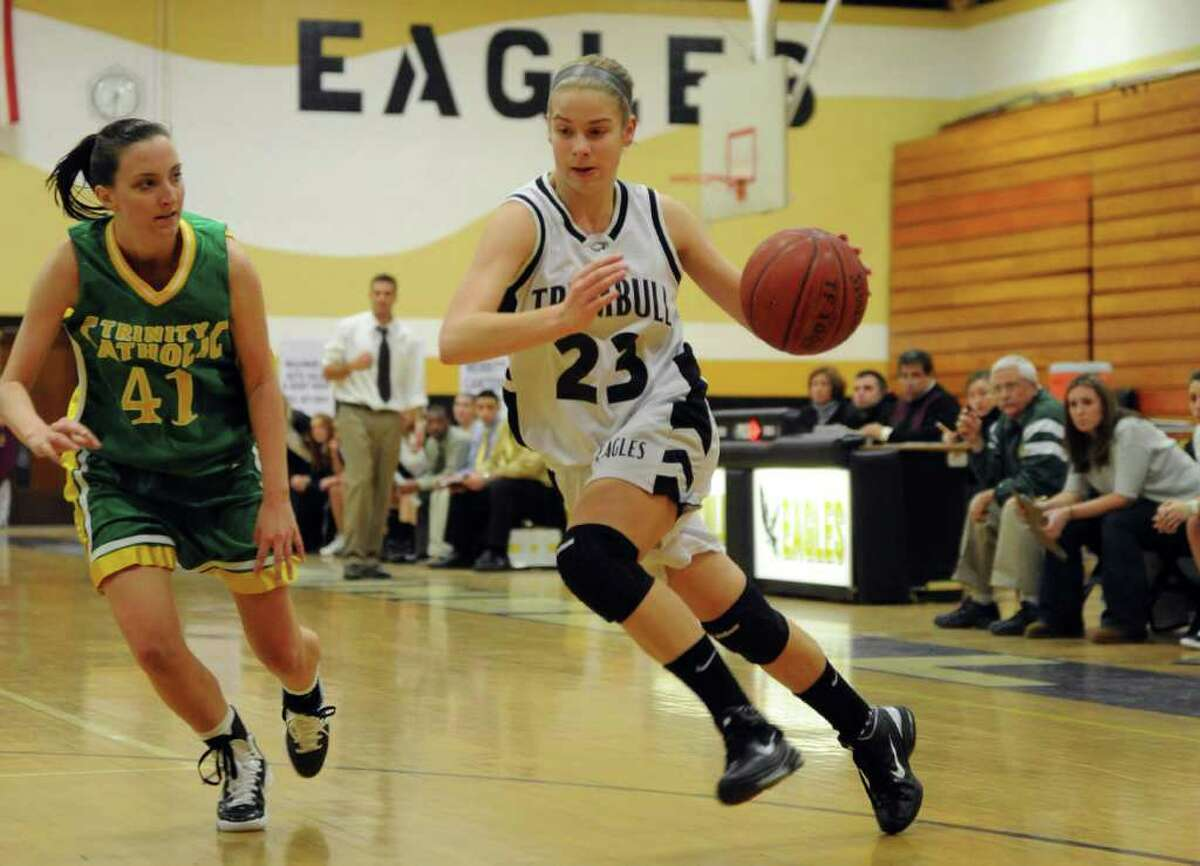 Trumbull's Victoria Pfohl dribbles around Trinity Catholic's Kelly Andersen during Friday's game at Trumbull High School on January 14, 2011.