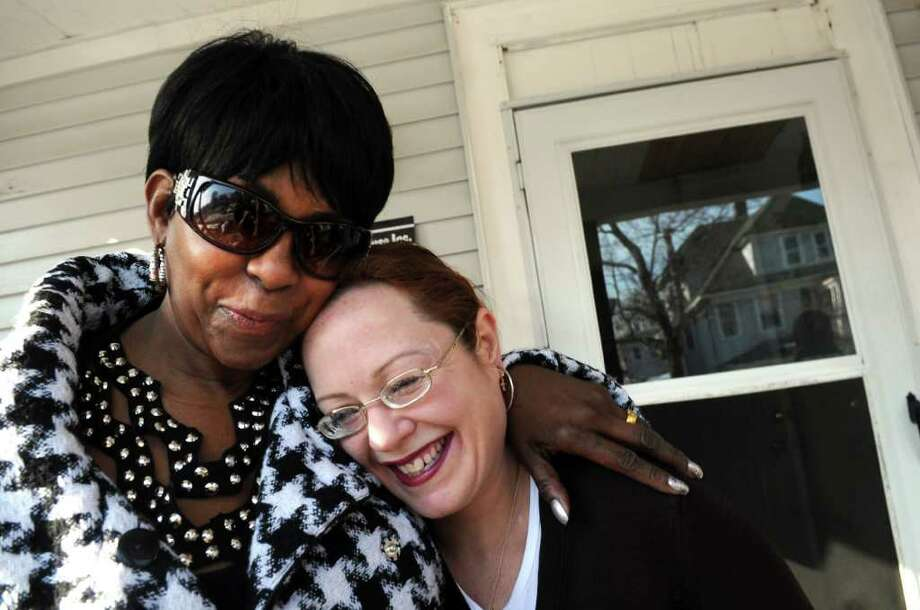 "Founder Debra McLemore (Mrs. Mack) embraces resident Jesse Amber Stone  Thursday, Feb. 17, 2011 on the porch of Miracle House, a transitional home for women, in Bridgeport.  Stone, who has lived at Miracle House for 3 months, believes ""Mrs. Mack is the miracle in Miracle House."" Photo: Autumn Driscoll / Connecticut Post"