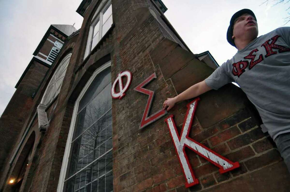 Ori Berger, a senior from Stanford, Calif., holds a replacement Sigma, a letter from the Greek alphabet, outside of the former St. Francis de Sales church, which was purchased by RPI's Phi Sigma Kappa fraternity from the Roman Catholic Diocese of Albany. The original Sigma letter placed outside of the church was vandalized. ( Philip Kamrass / Times Union )