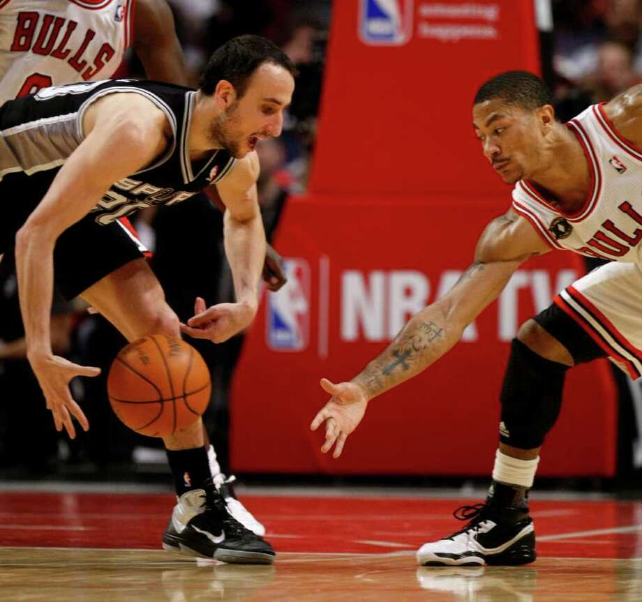 San Antonio Spurs guard Manu Ginobili, left, reaches for a loose ball as Chicago Bulls point guard Derrick Rose closes in during the second half of an NBA basketball game on Thursday, Feb. 17, 2011, in Chicago. Photo: AP