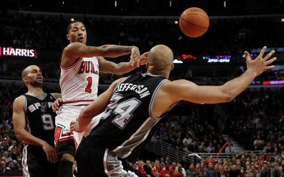 Chicago Bulls guard Derrick Rose, center, passes past the outstretched hand of San Antonio Spurs forward Richard Jefferson as Spurs' Tony Parker, left, watches during the second half of an NBA basketball game Thursday, Feb. 17, 2011, in Chicago. Rose scored a career-high 42 points in the Bulls' 109-99 win. Photo: AP