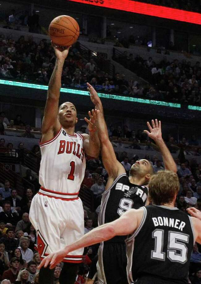Chicago Bulls guard Derrick Rose, left, shoots over San Antonio Spurs guard Tony Parker, center, and Matt Bonner during the second half of an NBA basketball game Thursday, Feb. 17, 2011, in Chicago. Rose scored a career-high 42 points in the Bulls' 109-99 win. Photo: AP