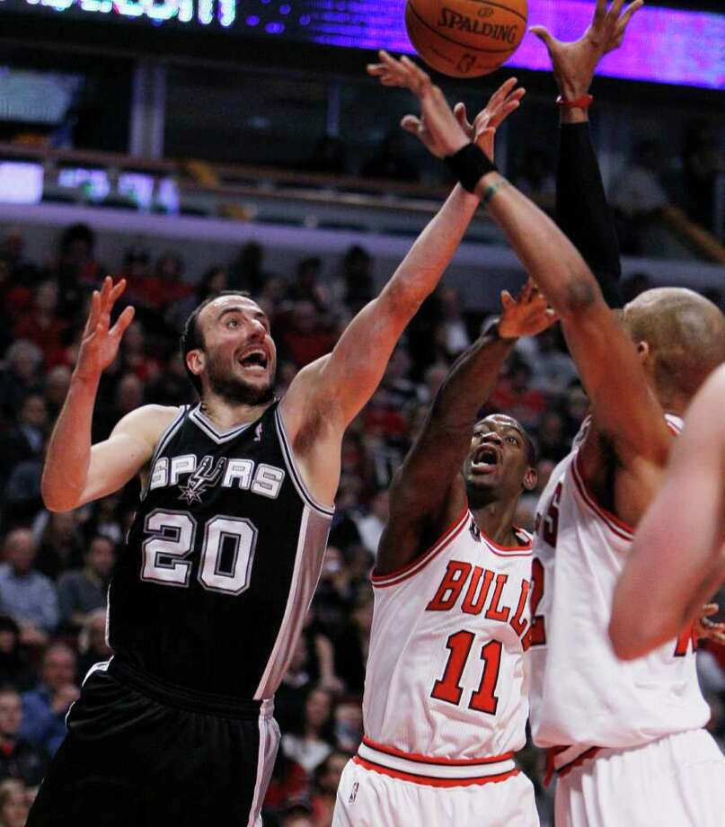San Antonio Spurs guard Manu Ginobili, left, shoots as Chicago Bulls' Ronnie Brewer, center, and Taj Gibson defend, during the first half of an NBA basketball game Thursday, Feb. 17, 2011, in Chicago. Photo: AP