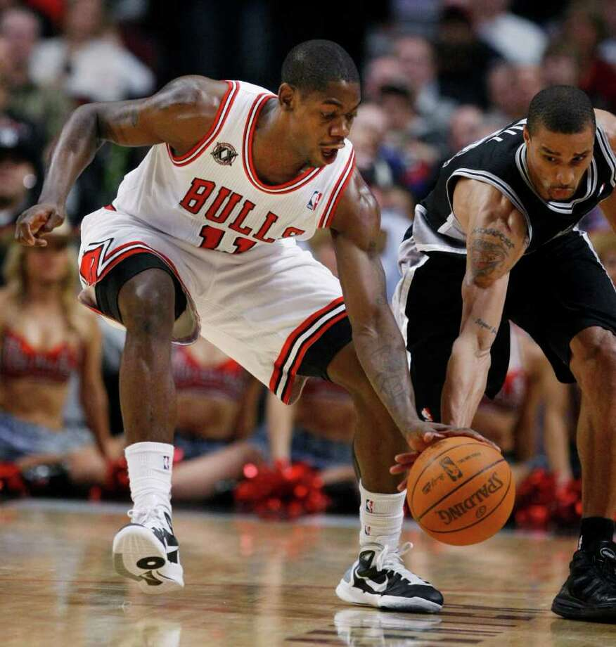 Chicago Bulls shooting guard Ronnie Brewer, left, battles San Antonio Spurs point guard George Hill for a loose ball during the first half of an NBA basketball game Thursday, Feb. 17, 2011, in Chicago. Photo: AP