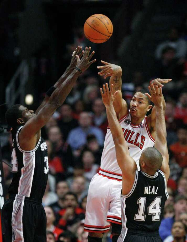 Chicago Bulls guard Derrick Rose, center, passes between the San Antonio Spurs defense of forward Antonio McDyess, left, and guard Gary Neal, during the first half of an NBA basketball game Thursday, Feb. 17, 2011, in Chicago. Photo: AP