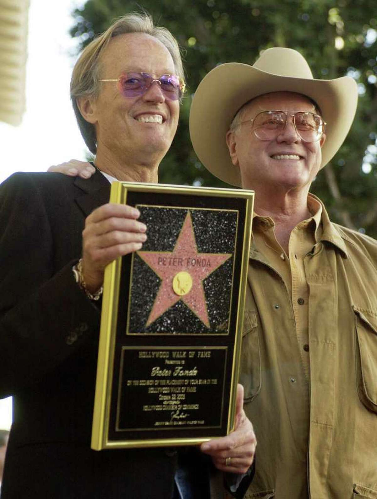 Actor-director Peter Fonda, left, is joined by actor Larry Hagman as he holds a replica of his new star on the Hollywood Walk of Fame in Los Angeles, Wednesday, Oct. 22, 2003. Hagman appeared in the television version of Fonda's 1971 film,