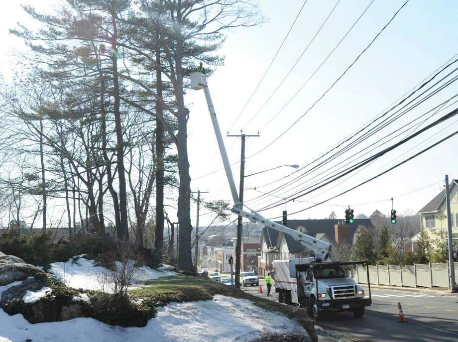 Sergo Cotto of Lewis Tree Service, riding in a bucket, uses a chain saw to take down tree limbs close to the power lines on East Putnam Avenue, Cos Cob, Friday afternoon, Feb. 18, 2011. Photo: Bob Luckey / Greenwich Time