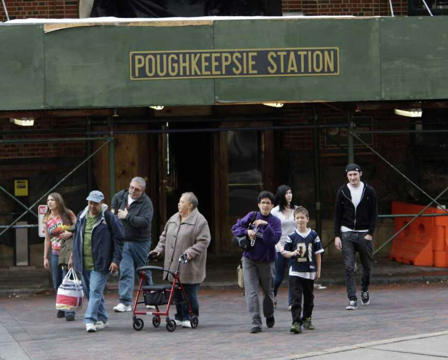 People walk outside the Poughkeepsie rail station in Poughkeepsie, N.Y., on Friday, Feb. 18, 2011.  Authorities say a police officer was shot and the gunman killed in a shootout near a train station in New York's Hudson Valley. Three other officers were hurt, but police haven't said what their injuries are. (AP Photo/Mike Groll) Photo: Mike Groll