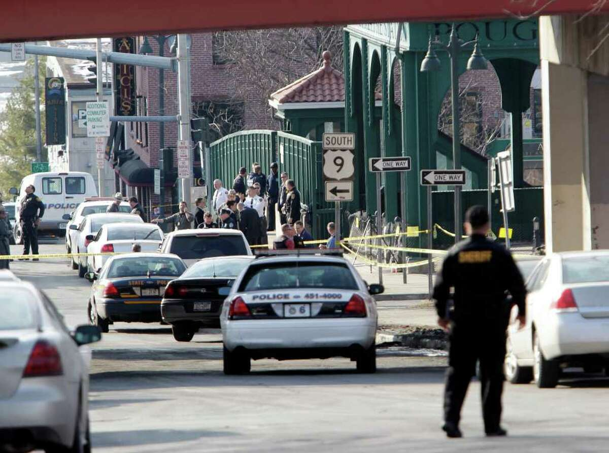 Law enforcement officers stand outside the Poughkeepsie rail station in Poughkeepsie, N.Y., on Friday, Feb. 18, 2011. Authorities say a police officer was shot and the gunman killed in a shootout near a train station in New York's Hudson Valley. Three other officers were hurt, but police haven't said what their injuries are. (AP Photo/Mike Groll)