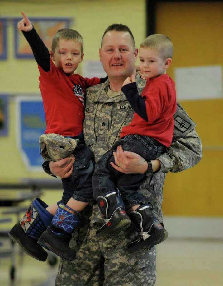 Sgt. Scott Potter holds sons Alexander, left, and Kadan as he enters Coeymans Elementary School. After so much time away, Potter will spend time celebrating Christmas and visiting his parents. (Skip Dickstein / Times Union) Photo: Skip Dickstein