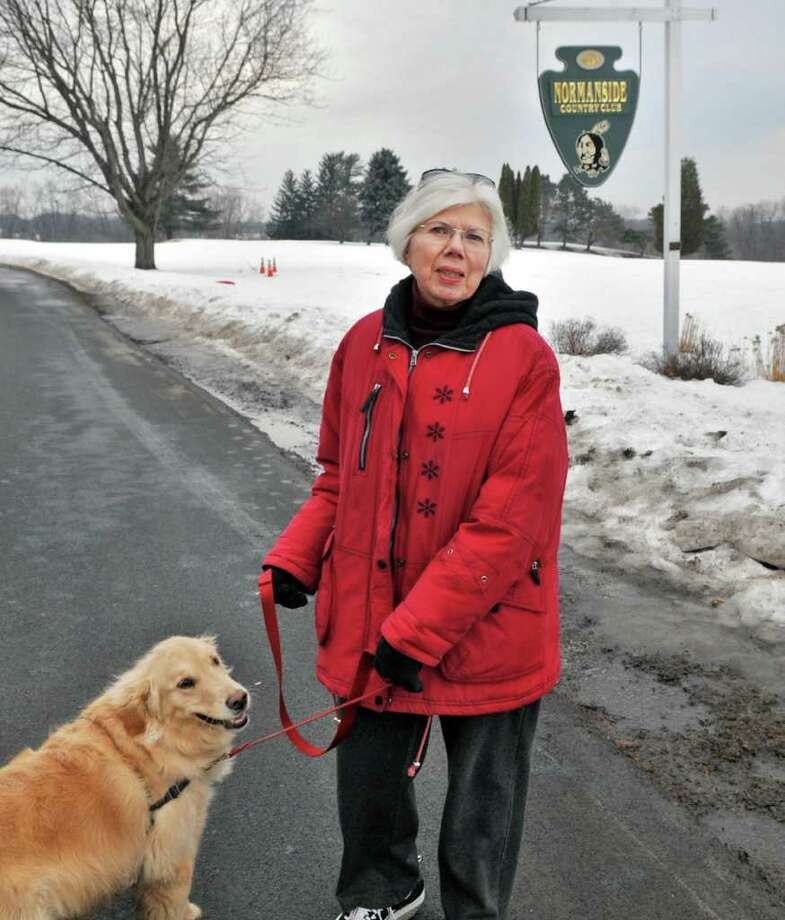 """Marti McSharry of Elsmere and her dog Zoe walk along Salisbury Road through the closed Normanside Country Club in Delmar Friday morning Feb. 18, 2011. McSharry feels strongly that the trees and open spaces should be preserved. """"It would be nice if the people of Bethlehem could benefit"""" from all this, she said. (John Carl D'Annibale / Times Union) Photo: John Carl D'Annibale / 00012132A"""