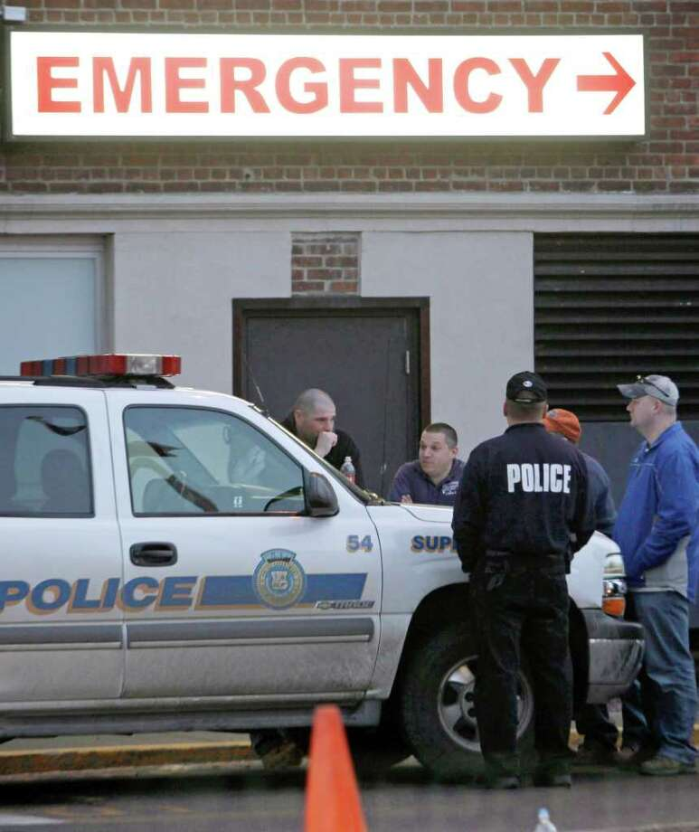 Law enforcement officers stand outside Vassar Brothers Medical Center in Poughkeepsie, N.Y. on Friday, Feb. 18, 2011 where a Poughkeepsie police officer was brought after a shooting incident on Friday. (AP Photo/Mike Groll) Photo: Mike Groll