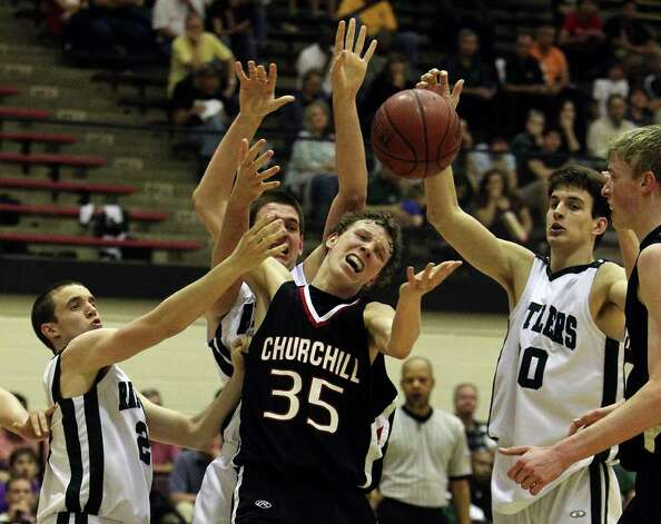 Churchill's Clark Lammert (35) struggles to grab a rebound against the trio of Reagan players: Sam Carlson (from left), Connor Knight and Brad Coulter in boys basketball at Littleton Gym on Friday, Feb. 18, 2011. Reagan defeated Churchill in overtime, 71-64. Photo: KIN MAN HUI, Kin Man Hui/kmhui@express-news.net / San Antonio Express-News