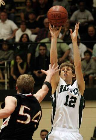 Reagan's Brandon Oxendine (12) shoots over Churchill's Connor Lammert (54) in boys basketball at Littleton Gym on Friday, Feb. 18, 2011. Reagan defeated Churchill in overtime, 71-64. Photo: KIN MAN HUI, Kin Man Hui/kmhui@express-news.net / San Antonio Express-News