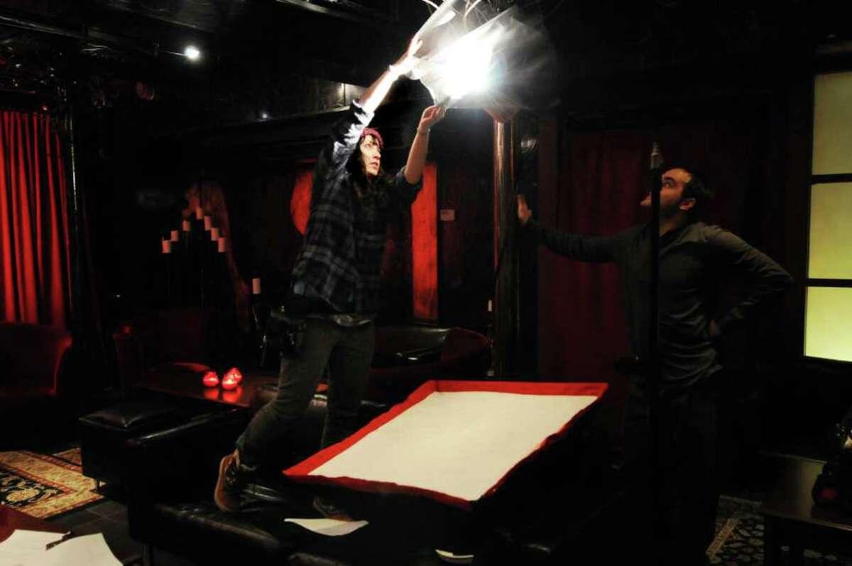 Cinematographer Lauren Kraus, center, works on the lighting before filming the web series