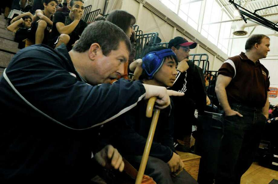 H.S. WRESTLING -- Win Myint, a 13-year-old wrestler for Rennselaer, talks with his coach, Mike Quinn, prior to a recent match at Maple Hill. (Michael P. Farrell / Times Union) Photo: Michael P. Farrell