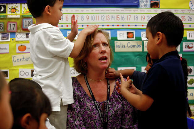 Jose Combs (from left), San Juana Avecilla and Joel Vasquez play with teacher Andrea Greimel at Carvajal Early Childhood Education Center. Photo: LISA KRANTZ/lkrantz@express-news.net / SAN ANTONIO EXPRESS-NEWS