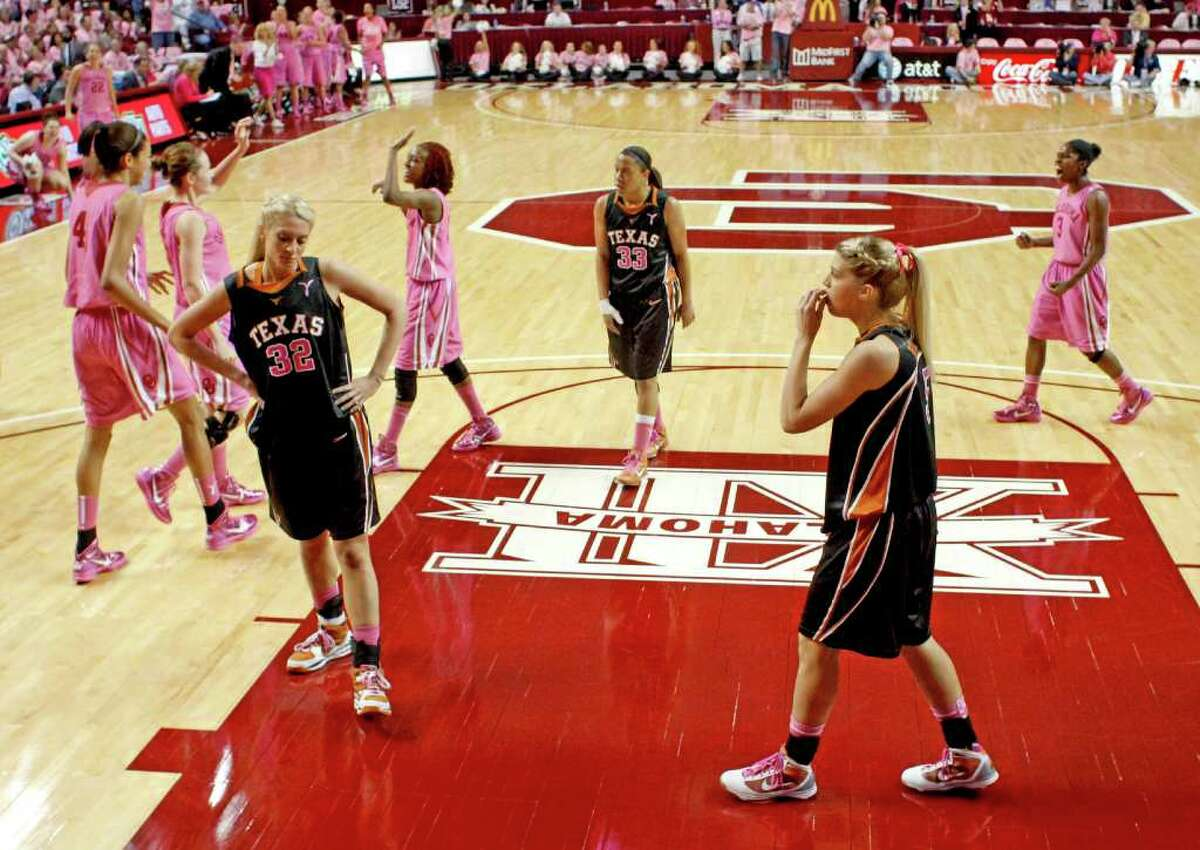 Oklahoma's Nicole Griffin (4), Whitney Hand (25), and Danielle Robinson (13) celebrate behind Texas' Kristen Nash (32), Ashleigh Fontenette (33) and Kathleen Nash (5) during the teams' meeting in Norman, Okla., on Saturday, Feb. 19, 2011.