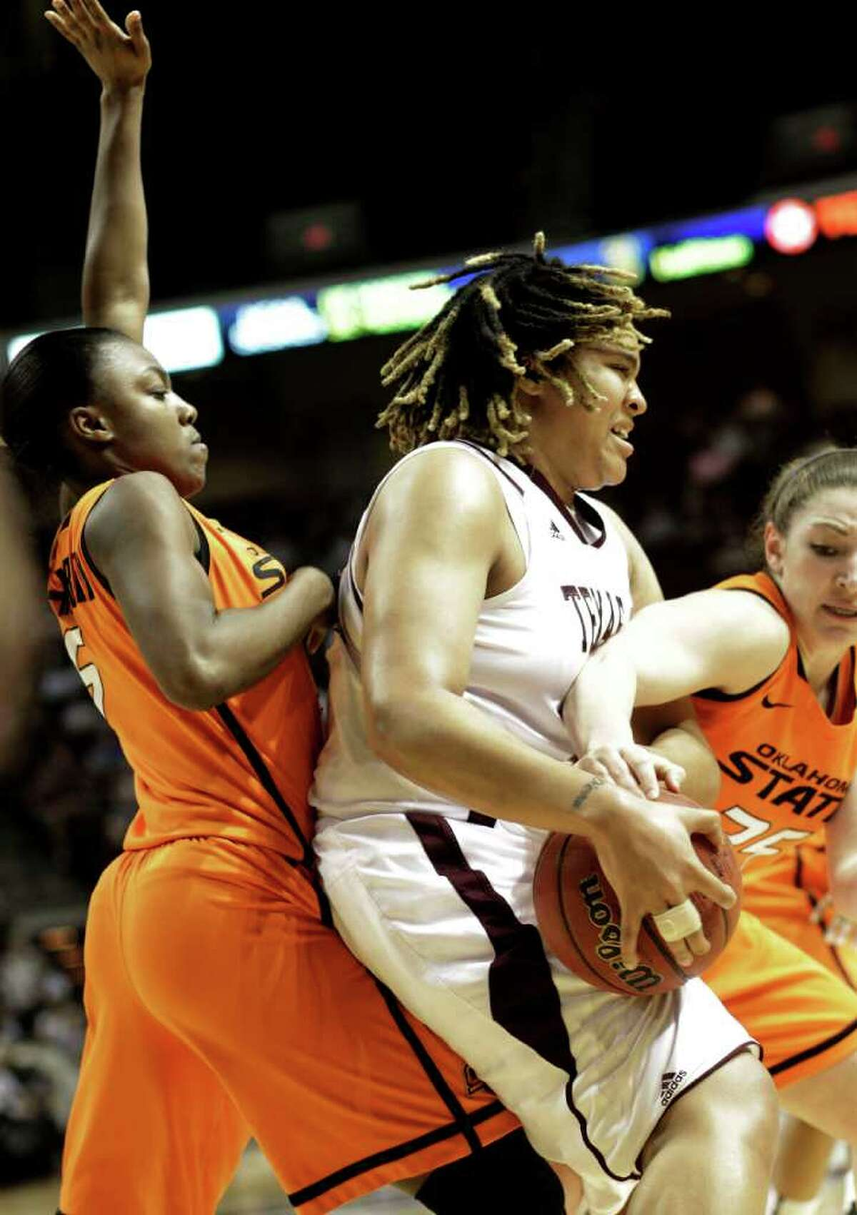 Texas A&M's Danielle Adams is sandwiched between Oklahoma State defenders Caroly Blair-Mobley (5) and Lindsey Keller (25) during the first half on Saturday, Feb. 19, 2011, in College Station.