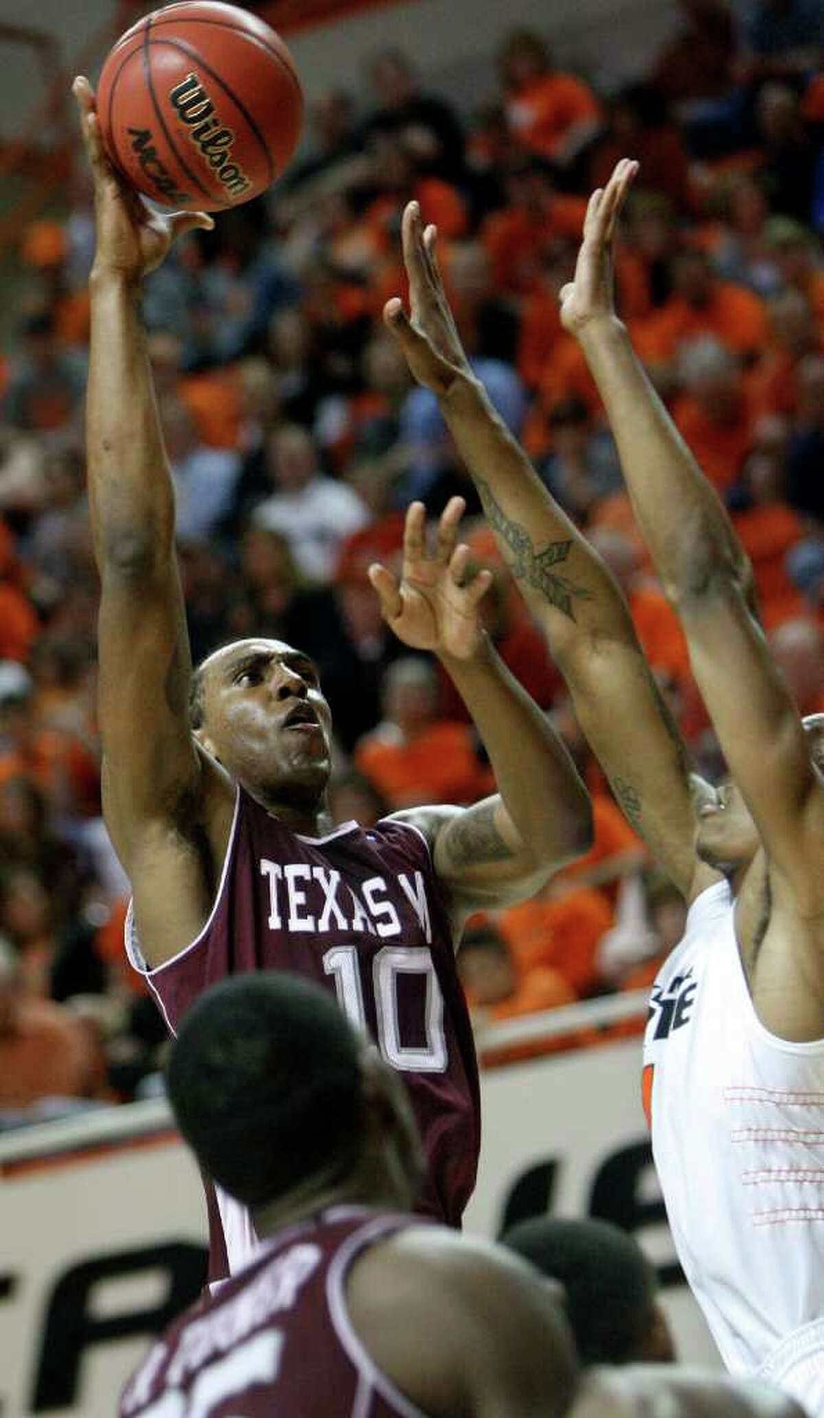 Texas A&M forward David Loubeau (left) shoots over Oklahoma State forward Jarred Shaw in the first half in Stillwater, Okla., on Saturday, Feb. 19, 2011.