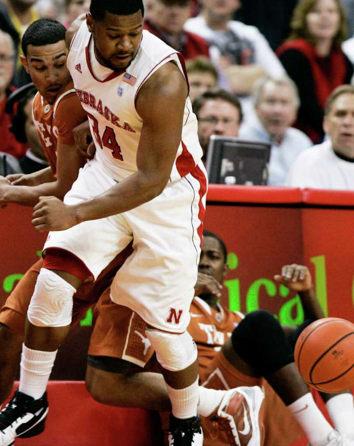 Texas' Cory Joseph (left) and Nebraksa's Lance Jeter chase after a loose ball during the first half in Lincoln, Neb., on Saturday, Feb. 19, 2011.