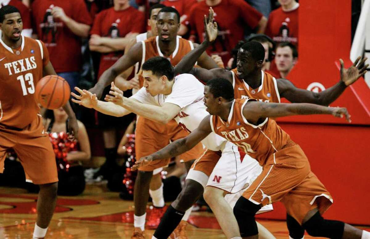 Nebraska's Jorge Brian Diaz (center) is defended by Texas' Tristan Thompson (13), Jordan Hamilton (center rear), Alexis Wangmene (right), and J'Covan Brown (14), in the first half in Lincoln, Neb., on Saturday, Feb. 19, 2011. Nebraska beat Texas 70-67.