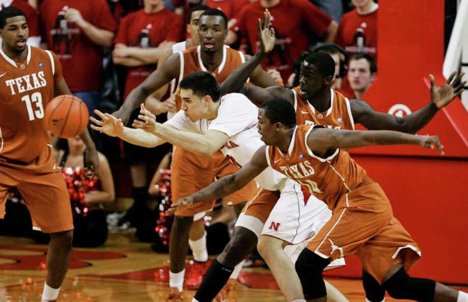 Nebraska's Jorge Brian Diaz (center) is defended by Texas' Tristan Thompson (13), Jordan Hamilton (center rear), Alexis Wangmene (right), and J'Covan Brown (14), in the first half in Lincoln, Neb., on Saturday, Feb. 19, 2011. Nebraska beat Texas 70-67. Photo: Nati Harnik, Associated Press
