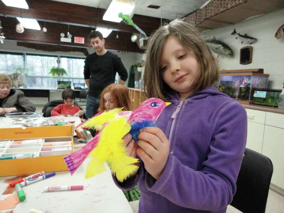 Audrey Luther, 8, of Norwalk, proudly shows the bird she decorated Saturday at Earthplace in Westport. While most children opted to make robins out of their paper bird cut-outs, Audrey preferred the more colorful features of an imaginery bird. Photo: Meg Barone / Westport News freelance
