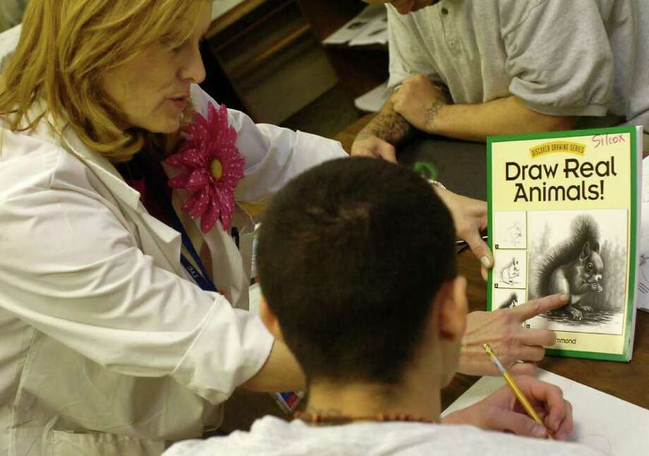 Art teacher Michelle Silcox points out a detail on the book the students were working from while learning to draw a squirell. Dave Ryan/The Enterprise Photo: Dave Ryan / Beaumont