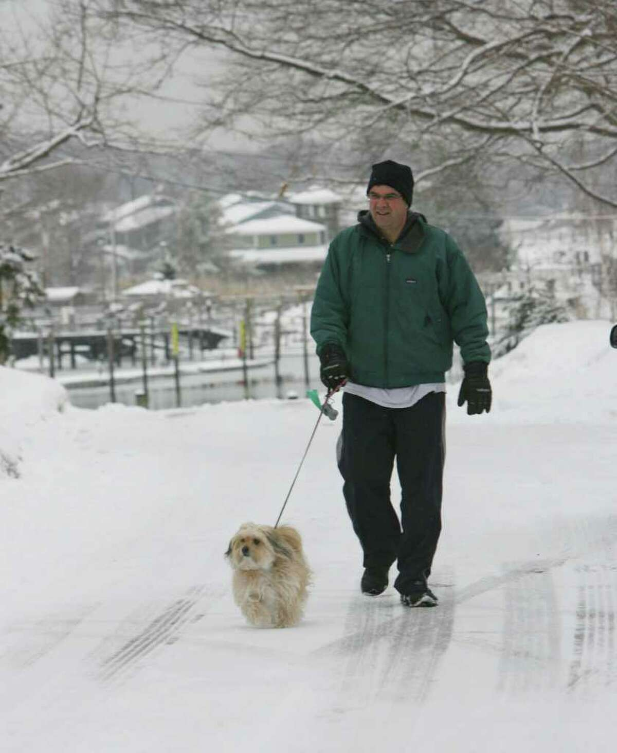 Dave Steinlauf walks his dog, Jingles, after a snow fall in Milford on Monday, Feb. 21, 2011.