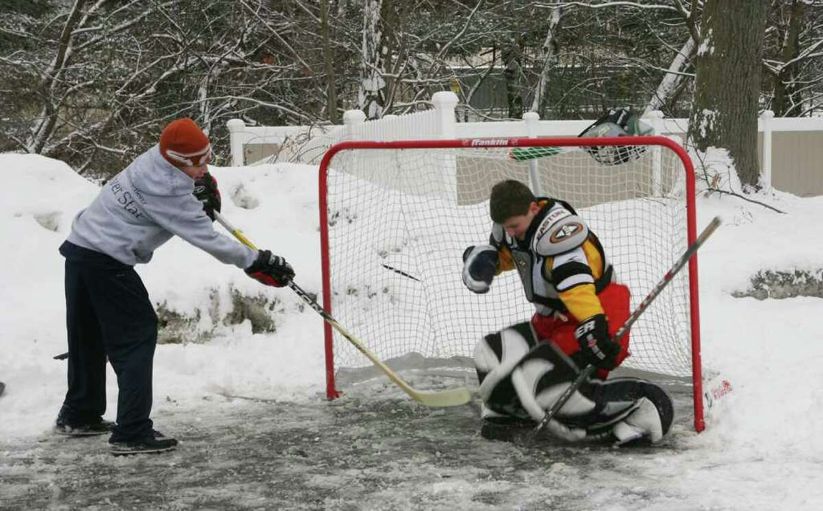 Rob Griswold, 12, takes a shot on Nick Catandella,12, on Briggs Court in Milford on Monday, Feb. 21, 2011. The boys were off from school for President's Day but lost the rest of their February vacation in order to make up snow days.