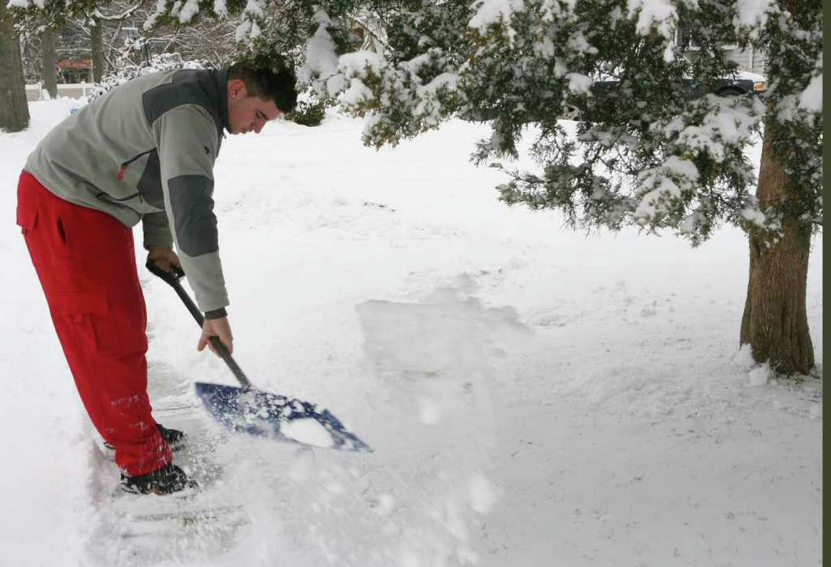 Mark Feola shovels a neighbors walkway after a snow fall in Milford on Monday, Feb. 21, 2011.