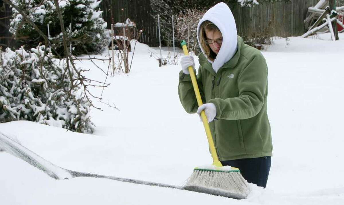Allison Wallace cleans her sister's car on Baxter St. after a snow fall in Stratford on Monday, Feb. 21, 2011.